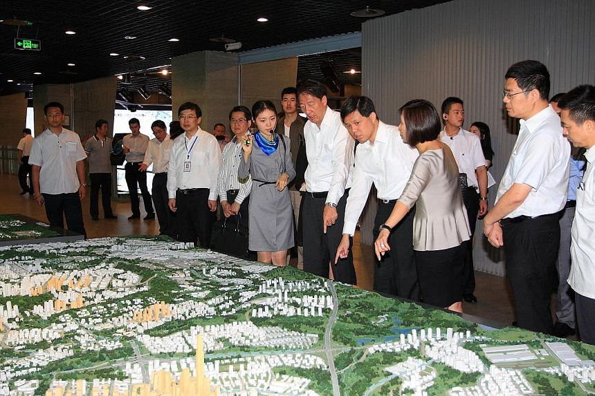 Deputy Prime Minister Teo Chee Hean and then Minister for Social and Family Development Chan being briefed on the Raffles City Chongqing project during a visit to China in July 2014. Mr Chan giving out red packets to some 130 senior citizens at a Chi