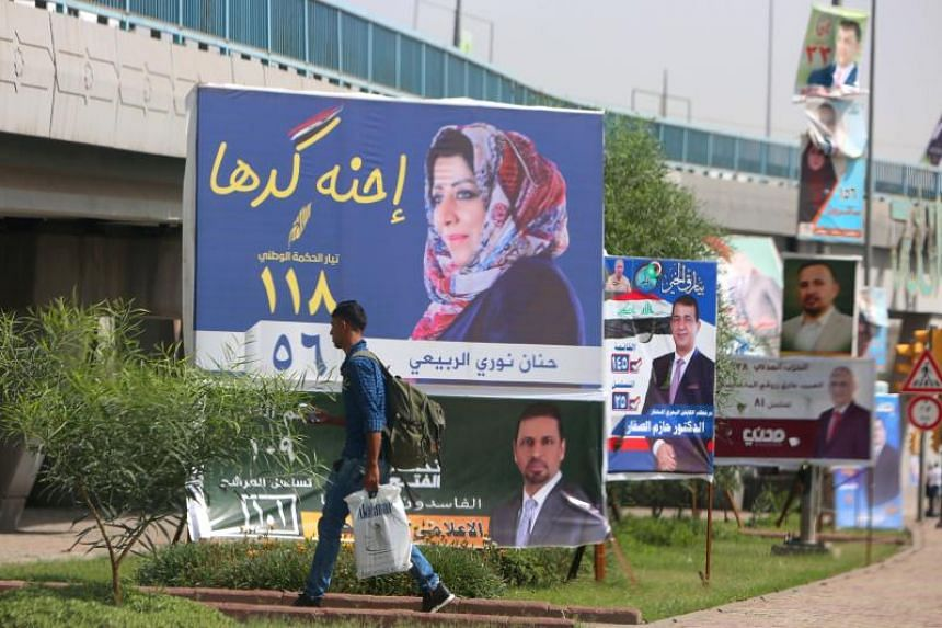 A man walks past electoral campaign posters in Baghdad on May 8, 2018.