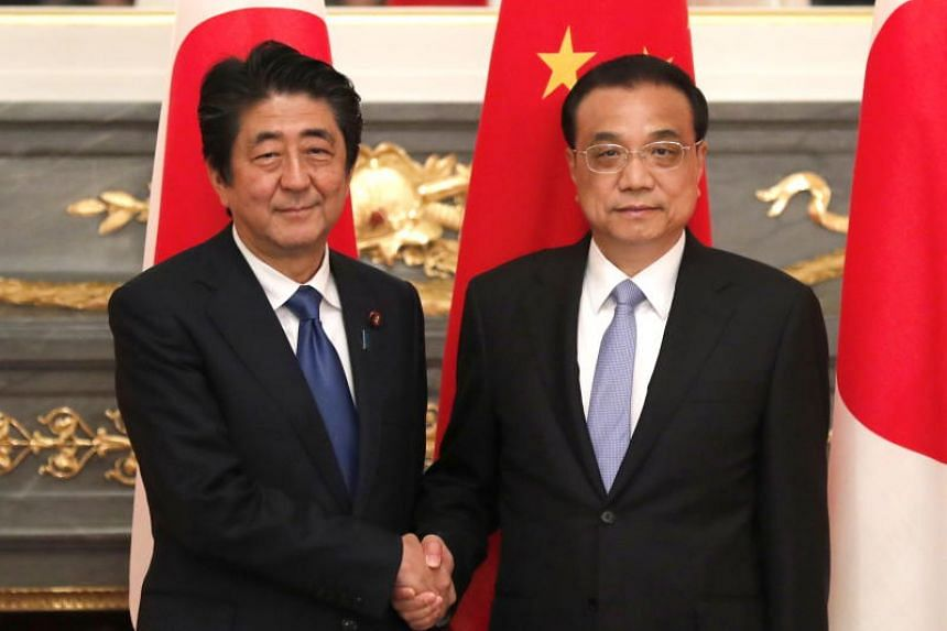 Japanese Prime Minister Shinzo Abe (left) and Chinese Premier Li Keqiang agreed to set up a hotline for defence officials to talk to each other during incidents involving each others' naval vessels or military aircraft.