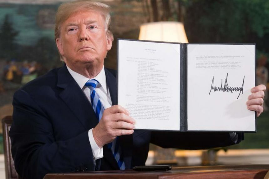 US President Donald Trump signs a document reinstating sanctions against Iran after announcing the US withdrawal from the Iran nuclear deal at the White House on May 8, 2018.
