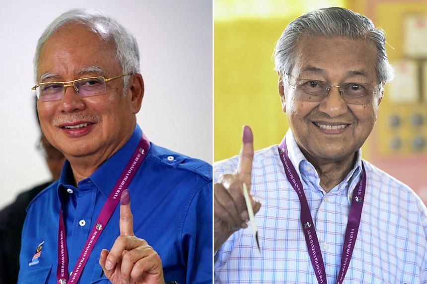Pakatan Harapan's candidate Mahathir Mohamad (right) and Malaysia's Prime Minister Najib Razak of Barisan Nasional showing their inked fingers after casting their votes on May 9, 2018.