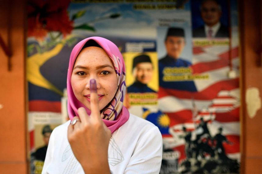A Malaysian woman poses with her inked finger after casting her vote during the 14th general election, in front of posters of former prime minister Mahathir Mohamad and current Prime Minister Najib Razak, at a polling station in Kuala Lumpur, on May