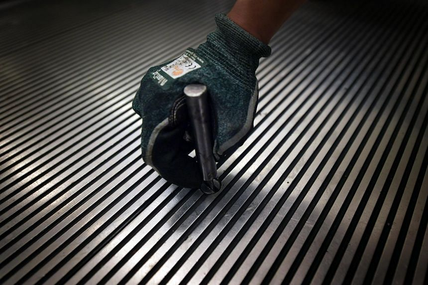 An escalator technician uses a floor plate lifting device to open the floor plate bolt of an escalator.