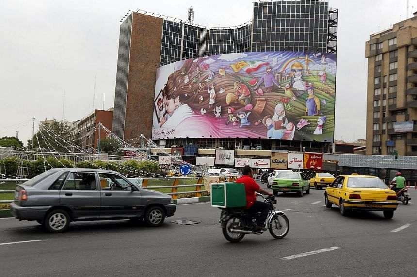 Iranians pass through Valiasr square in a street of the capital city of Tehran, Iran on May 8, 2018.