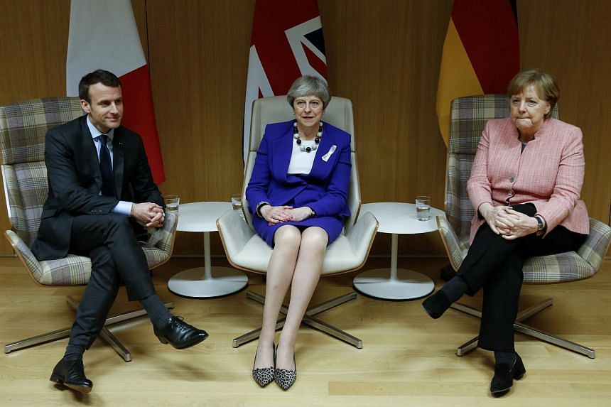 Britain's Prime Minister Theresa May (centre) with French President Emmanuel Macron (left) and German Chancellor Angela Merkel before their trilateral meeting at the European Union leaders summit in Brussels, Belgium on March 22, 2018.