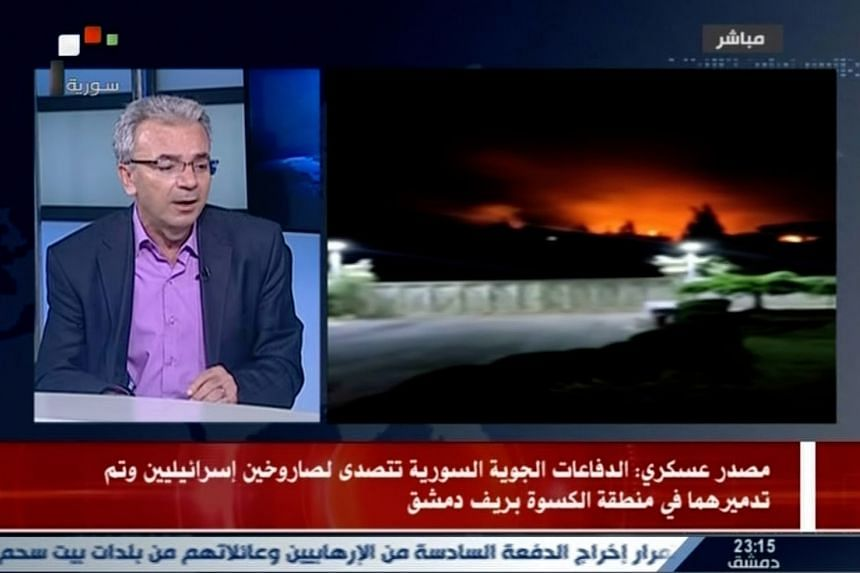 A television screengrab from a broadcast by the official Syrian Arab News Agency shows a Syrian presenter speaking with images on the right purportedly showing the aftermath of two intercepted Israeli missiles on May 8, 2018.