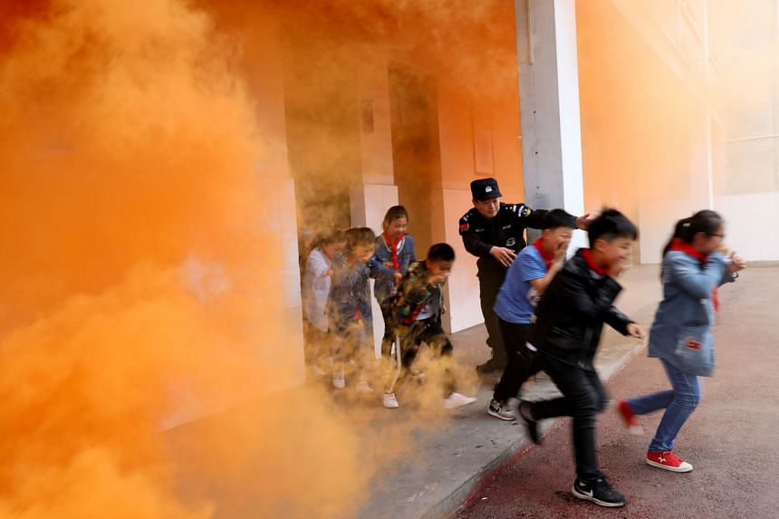 Primary school pupils taking part in an anti-terrorism drill in Huaibei, Anhui province, on Monday, aided by a police officer. Since March 2015, after a series of violent mass attacks took place in China, parts of the country have begun conducting su