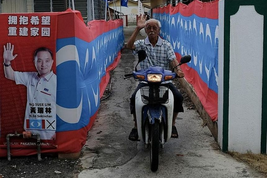 A motorcyclist making his way down a lane decorated with party flags in Sekinchan, a town in Selangor parliamentary ward Sungai Besar. Observers say the ward, held by BN after it won a 2016 by-election comfortably, could see a result closer to that i
