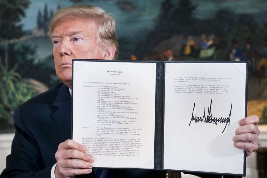 Trump signs a presidential memorandum on the Iran nuclear deal in the Diplomatic Room of the White House.