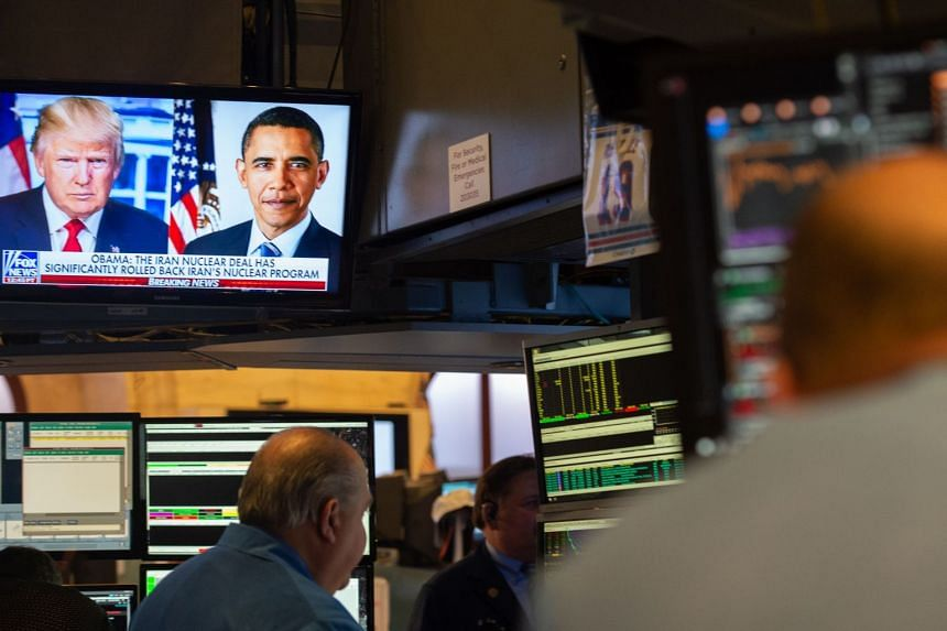 Trump and Obama portraits are on TV as traders work on the floor of the New York Stock Exchange.