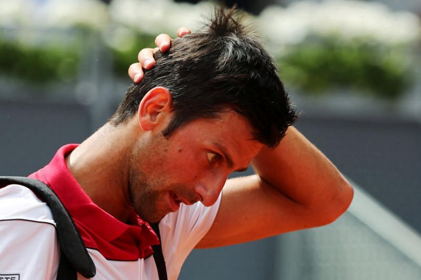Serbia's Novak Djokovic looks dejected after losing his second round match against Britain's Kyle Edmund in the Madrid Open on May 9, 2018.