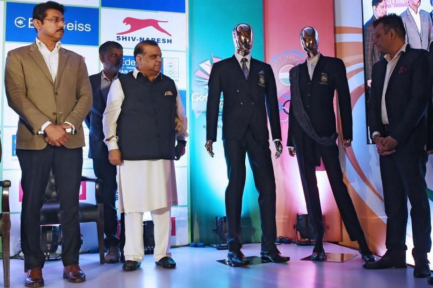 India's Minister of Youth Affairs and Sports Rajyavardhan Singh Rathore (left) and Indian Olympics Association president Narinder Dhruv Batra (second from left) unveil the official apparel for Indian athletes in New Delhi on Feb 26, 2018.