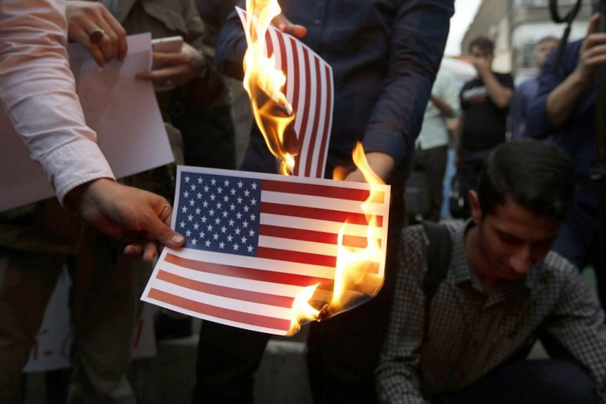 Iranians burn US and Israeli flags during an anti-US protest in Teheran, May 9, 2018.