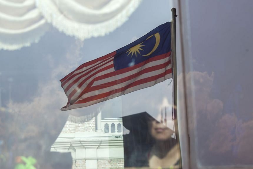A Malaysian flag is reflected on a bus window in Kuala Lumpur, May 8, 2018.