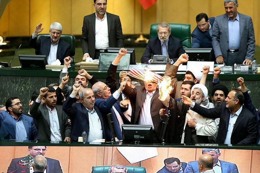 Iranian lawmakers burning a US flag in Parliament in Teheran yesterday. Mr Trump has announced that the US would exit the nuclear deal and reimpose sanctions on Iran. Mr Rouhani said the deal could survive without the US, and has directed diplomats t