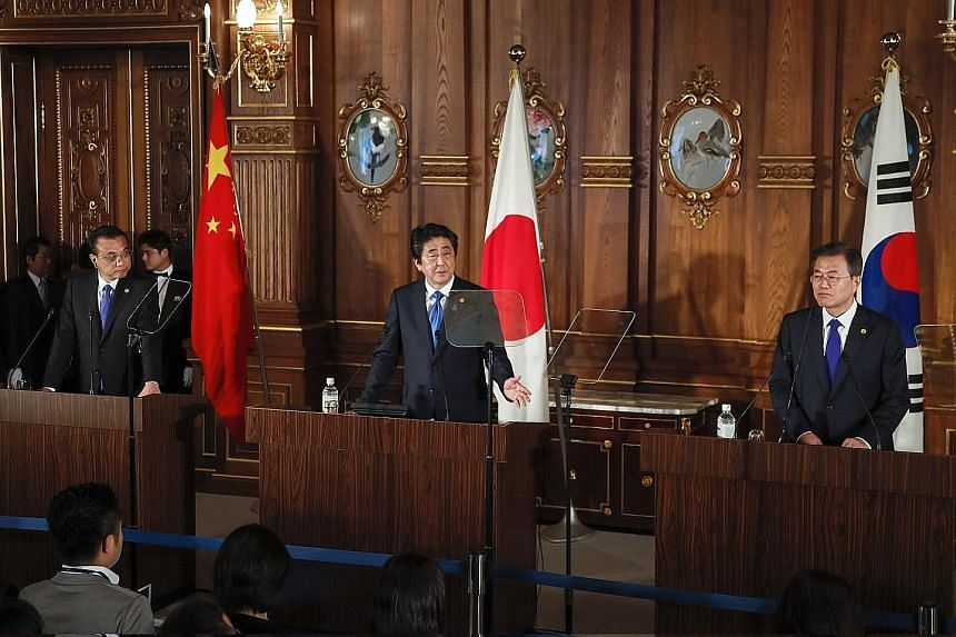 From far left: Chinese Premier Li Keqiang, Japanese Prime Minister Shinzo Abe and South Korean President Moon Jae In at a news conference after holding talks in Tokyo yesterday. The three leaders stuck largely to broad strokes without diving into the