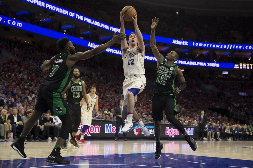 T.J. McConnell of the Philadelphia 76ers shoots the ball against Jaylen Brown #7 and Terry Rozier #12 of the Boston Celtics in the fourth quarter during Game Four of the Eastern Conference Second Round of the 2018 NBA Playoffs at Wells Fargo Center i