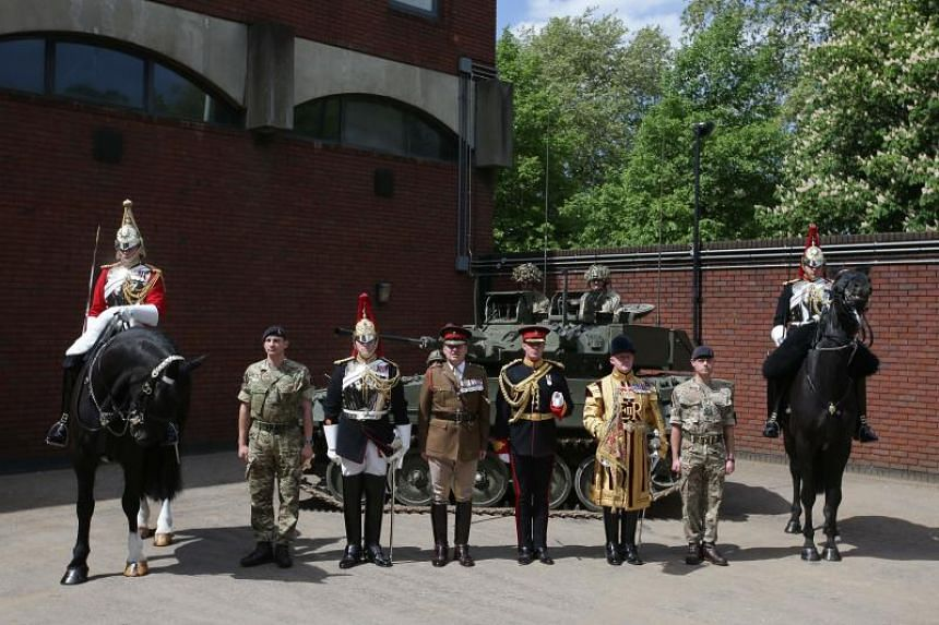 Members of the Household Cavalry Mounted Regiment, soldiers from the Household Cavalry Regiment with an armoured vehicle, Commanding Officer Lieutenant Colonel James Gaselee (centre) and a State Trumpeter of the Household Cavalry Band pose at the Hou