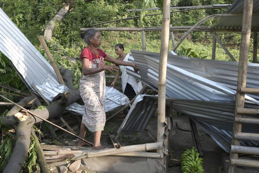 Indian women remove the tin sheets from their houses which was destroyed by strong winds and thunder storm, on the outskirts of Guwahati, Assam, India, May 9, 2018.