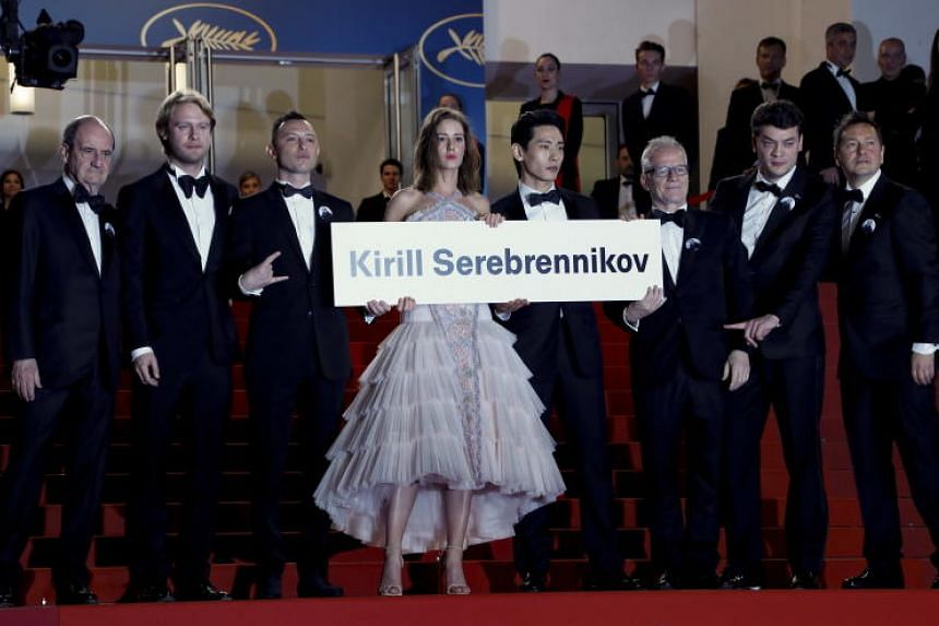 The cast from the movie hold a sign to free Director Kirill Serebrennikov as they arrive for the screening of Leto during the 71st annual Cannes Film Festival, in Cannes, France, May 9, 2018.