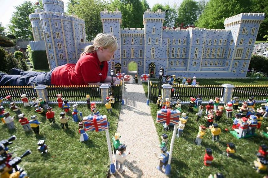 Legoland employee, Lucy, poses putting a Lego model of US actress Meghan Markle in place next to her husband-to-be Britain's Prince Harry outside a Lego-brick model of Windsor Castle at Legoland in Windsor on May 8, 2018.