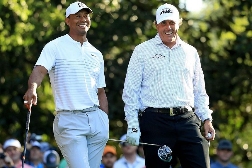 Tiger Woods (left) and Phil Mickelson talk on the 11th hole during a practice round prior to the start of the 2018 Masters Tournament at Augusta National Golf Club on April 3, 2018.