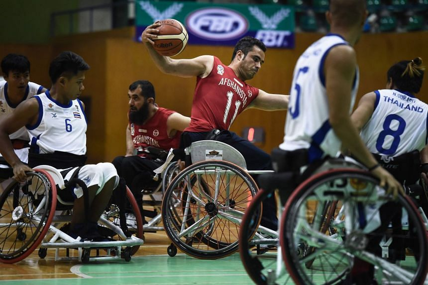 A member of Afghanistan's men's wheelchair basketball team (in red) playing against Thailand during the qualifying tournament for the Asian Para Games in Bangkok on March 4, 2018.