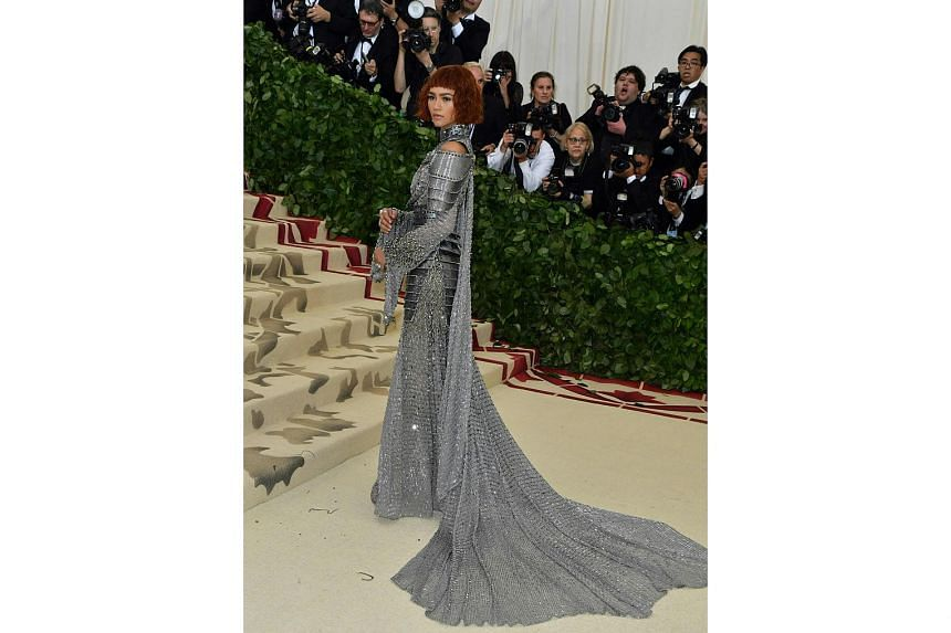 Pop star Rihanna sparkles in a Maison Margiela silver embroidered and spangled ensemble with a matching hat, while singer Zendaya (above) channels her inner Joan of Arc in an Atelier Versace outfit.