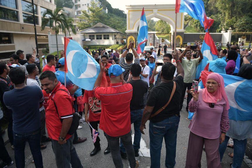 Pakatan Harapan supporters wait outside the Istana Negara on May 10, 2018.