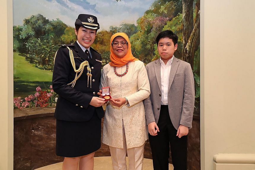 President Halimah Yacob presenting Major Rachel Lim Tszu-Yin - who has been an honorary aide-de-camp for 15 years - with a special token of appreciation at the Istana event last night. With them is Maj Lim's son Jonathan Chia, 12.
