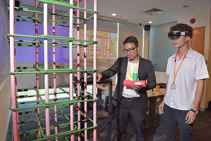 ITE civil and structural engineering design student Chia Jia Han (right) wears a hololens device to inspect a physical model against a virtual model under Trimble technical specialist Marvin Garcia's guidance at the Integrated Digital Delivery centre