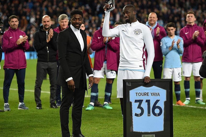Manchester City's Ivorian midfielder Yaya Toure holds up a memento presented to him by his brother Kolo after the 3-1 win against Brighton on Wednesday.