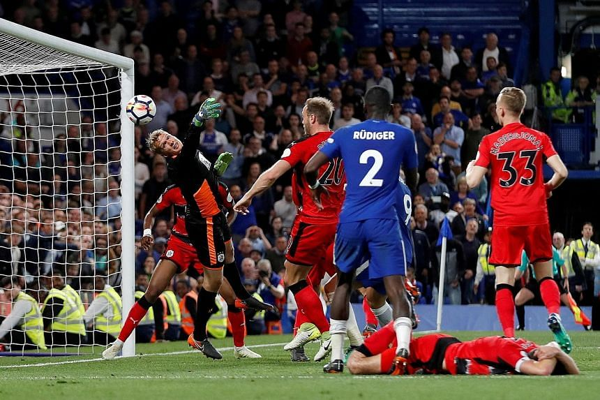 Huddersfield goalkeeper Jonas Lossl makes a survival-sealing save during the 1-1 draw against Chelsea on Wednesday. The Dane tipped Andreas Christensen's (not pictured) header onto the post in the 83rd minute.