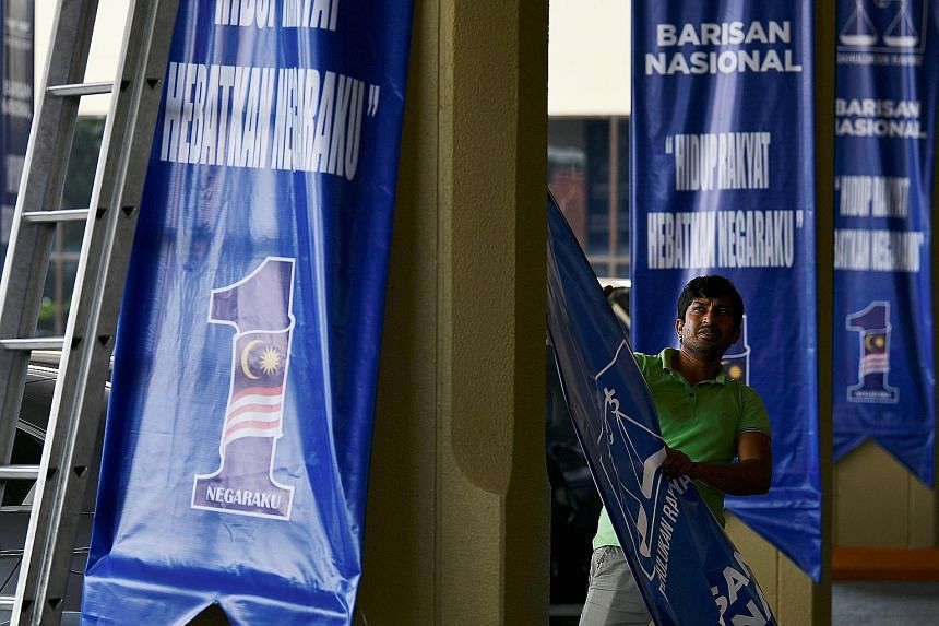 A worker removing a Barisan Nasional banner in Kuala Lumpur yesterday. Eight of the 12 elections to state assemblies on Wednesday yielded clear winners, and as of last night, three menteris besar had been formally named - in Kelantan, Terengganu and