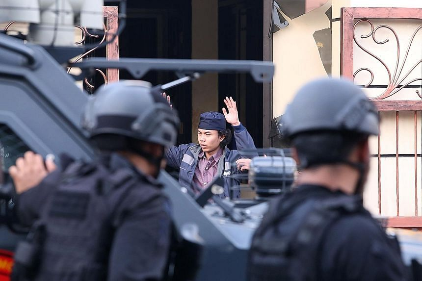 Top: An inmate surrendering to police after the prison riot in Kelapa Dua, 25km from Jakarta's city centre. Above: Firearms, ammunition and bulletproof gear used by the prisoners.