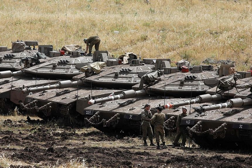 Israeli tanks seen near the Syrian border in the Israel-annexed Golan Heights yesterday. Israel's army said it had carried out raids against Iranian targets in Syria overnight after rocket fire towards its forces that it blamed on Iran.