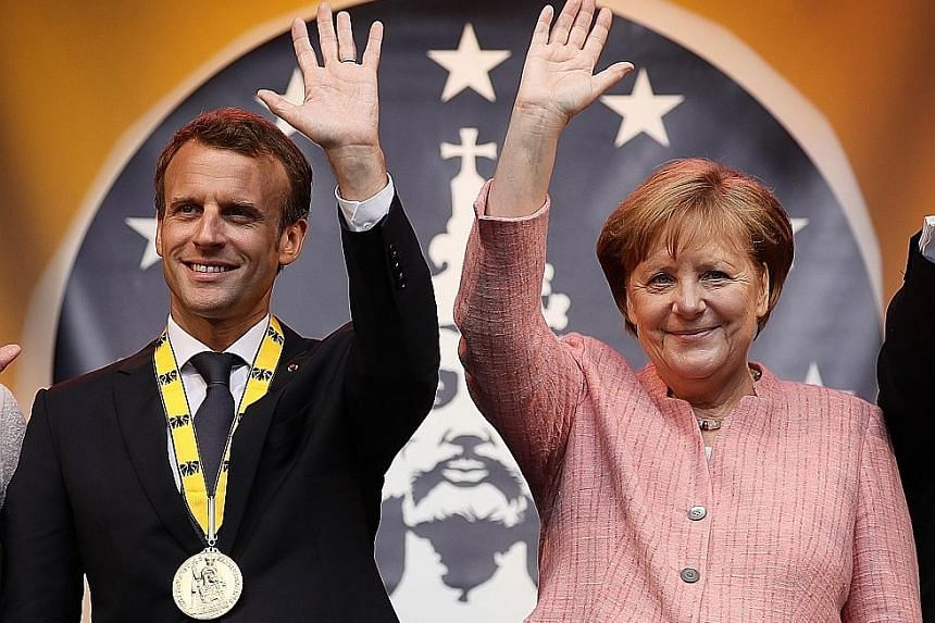 French President Emmanuel Macron, who received the prestigious Charlemagne Prize for strengthening European integration, on stage with German Chancellor Angela Merkel after the ceremony in Aachen, Germany, yesterday.