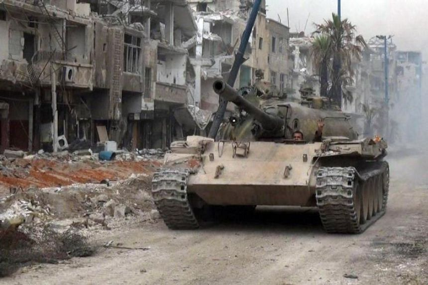 A Syrian army tank advancing through a street in al-Hajar al-Aswad as they push against the Islamic State (IS) group in the area on the southern outskirts of the capital Damascus on May 10, 2018.