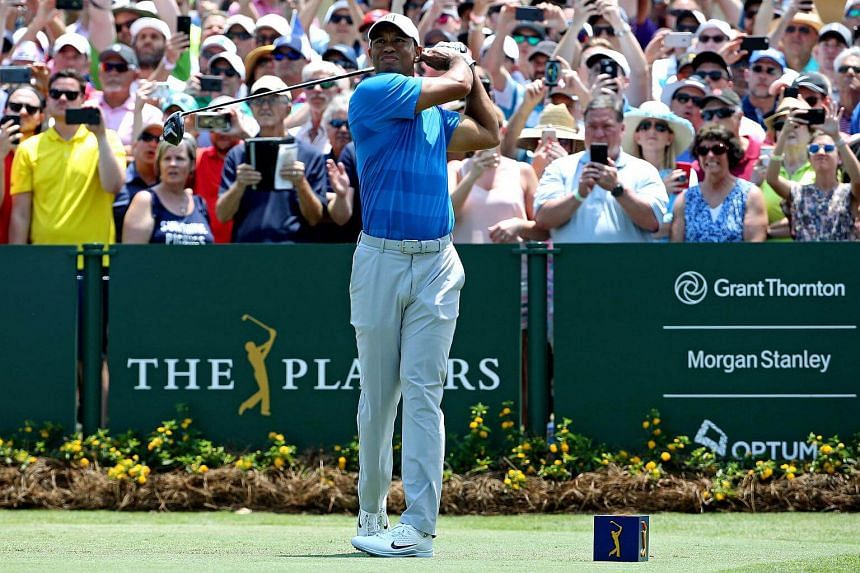 Tiger Woods plays a shot from the first tee during the first round of The Players Championship golf tournament.