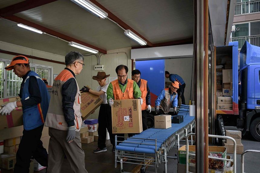 Park Jae Yeol (centre) sorts packages at an apartment complex in Seoul on May 10, 2018.