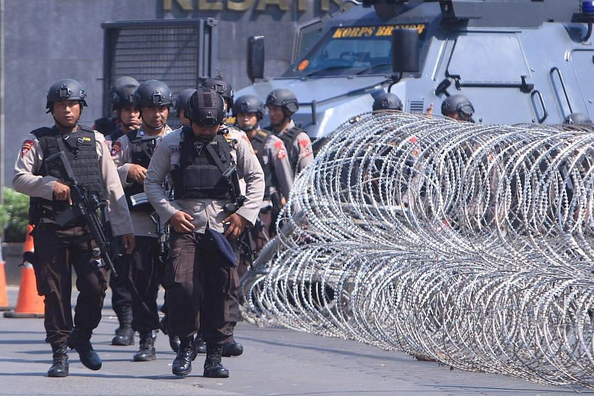 Armed members of the Indonesian Mobile Brigade Corps walk past barbed wire placed in front of a gate of the Mobile brigade police headquarters in Depok, Indonesia on May 9, 2018.