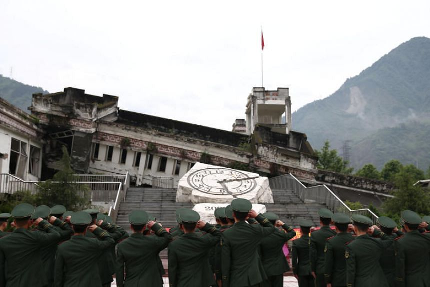 Paramilitary police officers attend a memorial event at Xuankou Middle School, now a memorial site for the 2008 Sichuan earthquake, a day before its 10th anniversary in Sichuan, China on May 11, 2018.