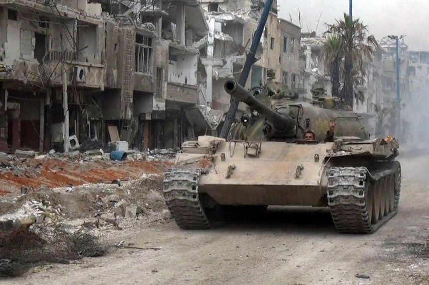 A Syrian army tank advances during a push against ISIS on the outskirts of Damascus.