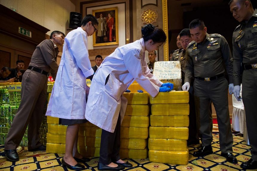 Thai national police chief general Chaktip Chaijinda (second from right) watches police department chemists inspect seized drugs during a press conference in Bangkok, on May 11, 2018.