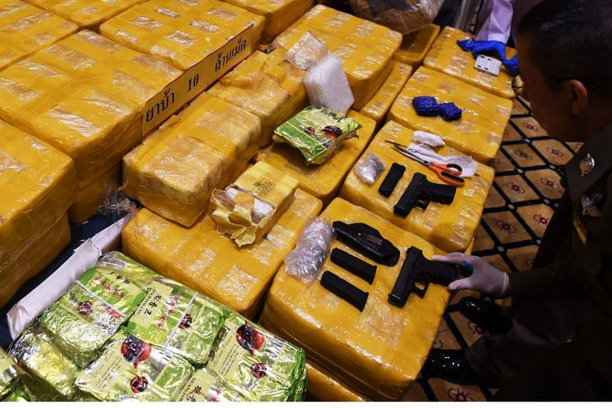 A police officer inspects seized drugs and guns during a press conference in Bangkok, on May 11, 2018.