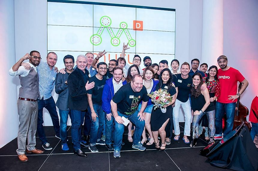 Muru-D Singapore head Paul Meyers (front) with members of the 10 graduating start-ups. Under the programme backed by Australian telco Telstra, Singapore firms CarePod, Idem Hospitality, Know and Vybes each got $75,000 in funding, mentorship, training