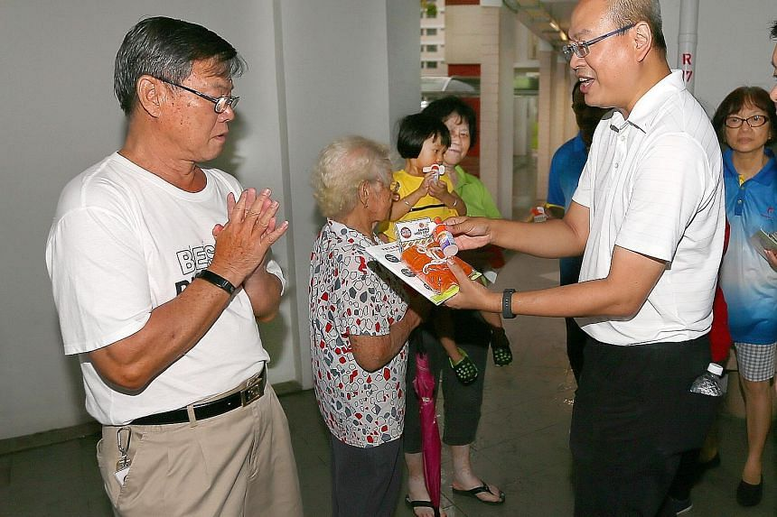 Mr Kok Choy Sing (left), a 68-year-old retiree, received bamboo pole covers and insect repellent from MP Yee Chia Hsing last night at the void deck of Block 953 Jurong West Street 91.