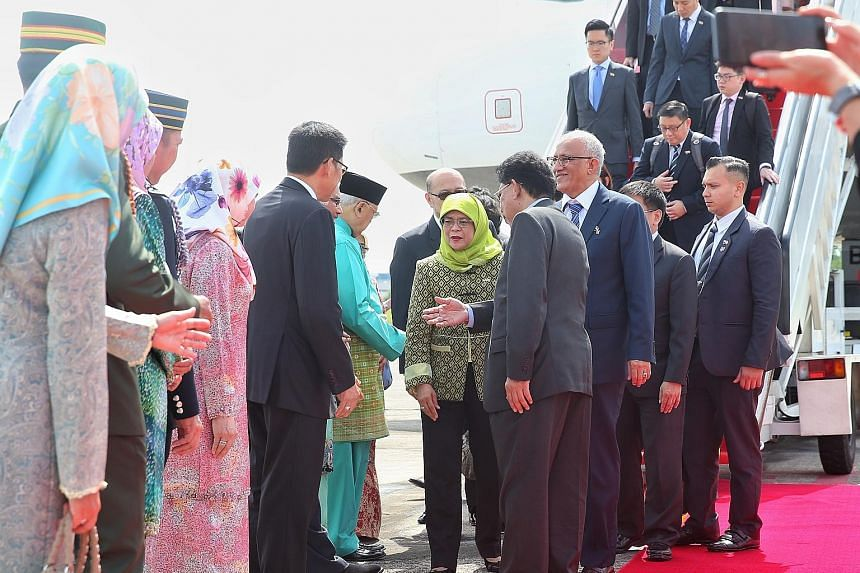 President Halimah Yacob and her husband, Mr Mohamed Abdullah Alhabshee, being received by officials at the Brunei International Airport yesterday. The President is in Brunei on a four-day state visit. Today, Madam Halimah will meet Sultan Hassanal Bo