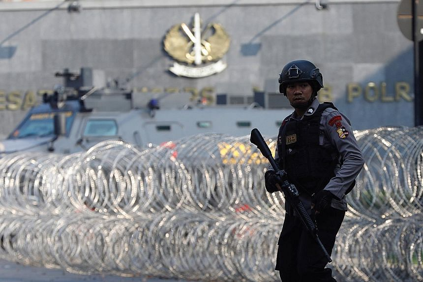 Jemaah Ansharut Daulah founder Aman Abdurrahman was among the inmates at the jail. A policeman patrolling near an armoured vehicle at the Mobile Police Brigade headquarters in Depok, Indonesia, on Thursday.