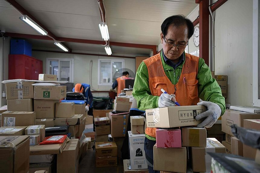 Mr Park Jae Yeol, 71, on Thursday sorting packages at an apartment complex in Seoul before delivering them.